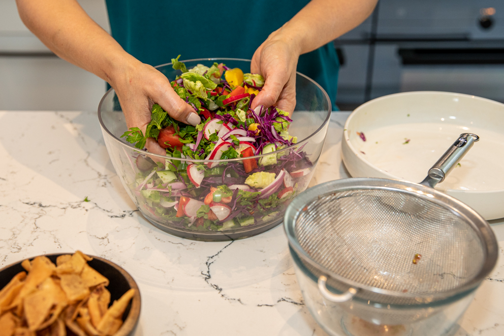 tossing the fattoush salad