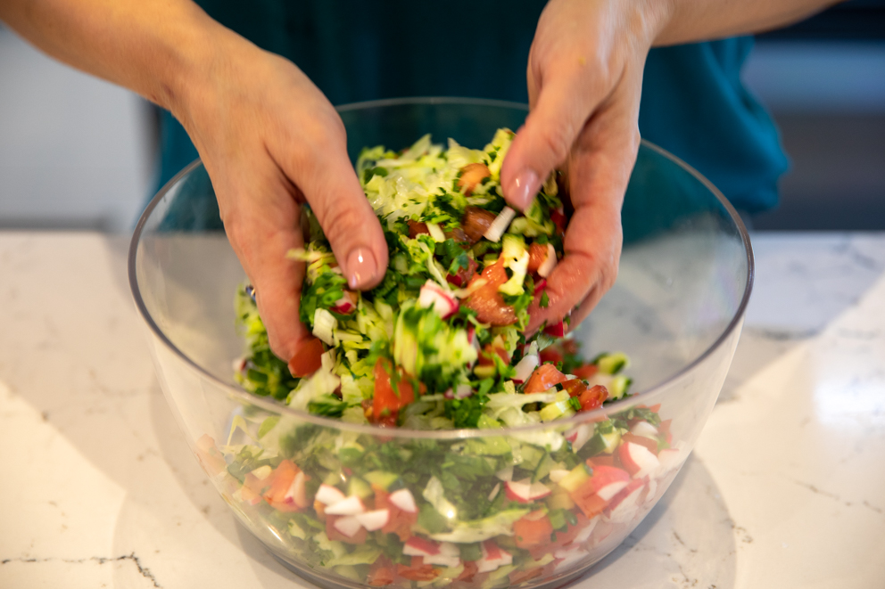 tossing the salad in a clear bowl