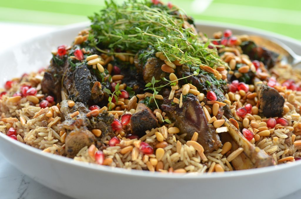 arabian nut rice with lamb shanks served in a white bowl