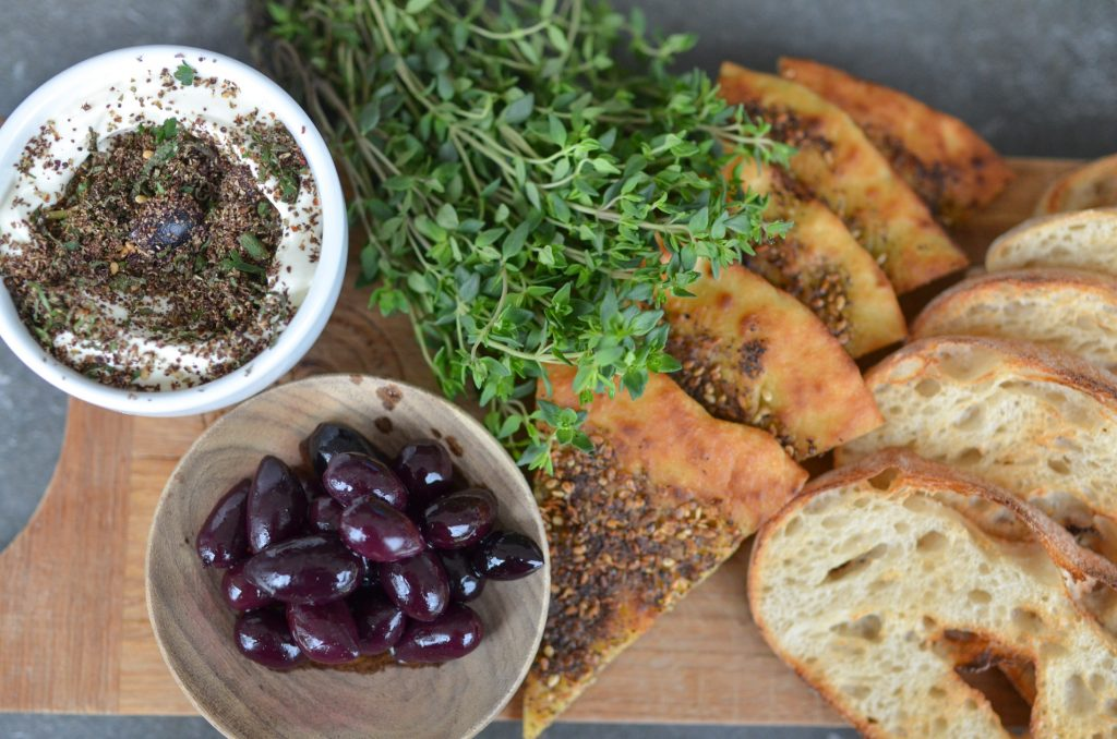 zaatar herb labneh served with herb pizza and olives