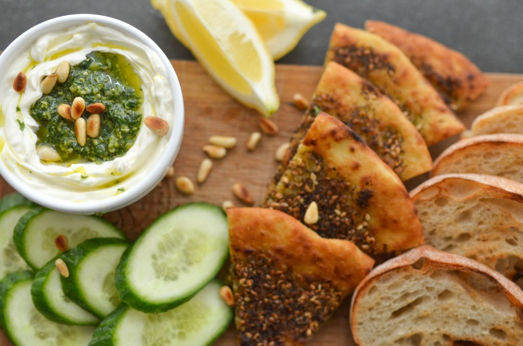 Pesto labneh - strained yogurt served on a board with za'atar herb pizza