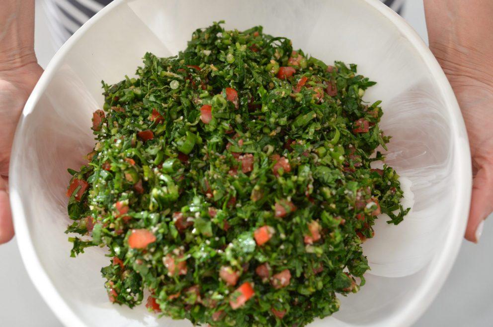 tabouli salad in a white dinosaur design bowl held by rouba shahin