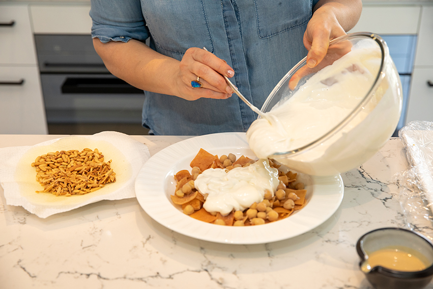 pouring yogurt on top of chickpea and crispy bread