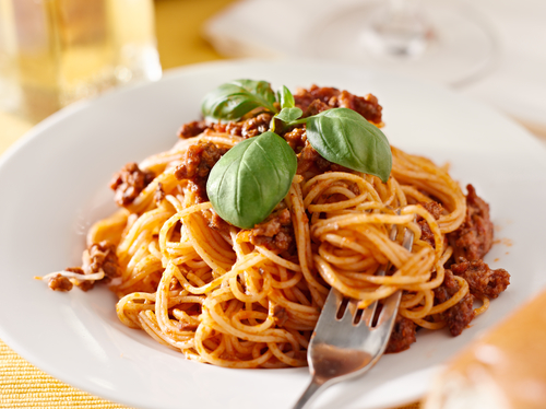 spaghetti with basil garnish in meat sauce