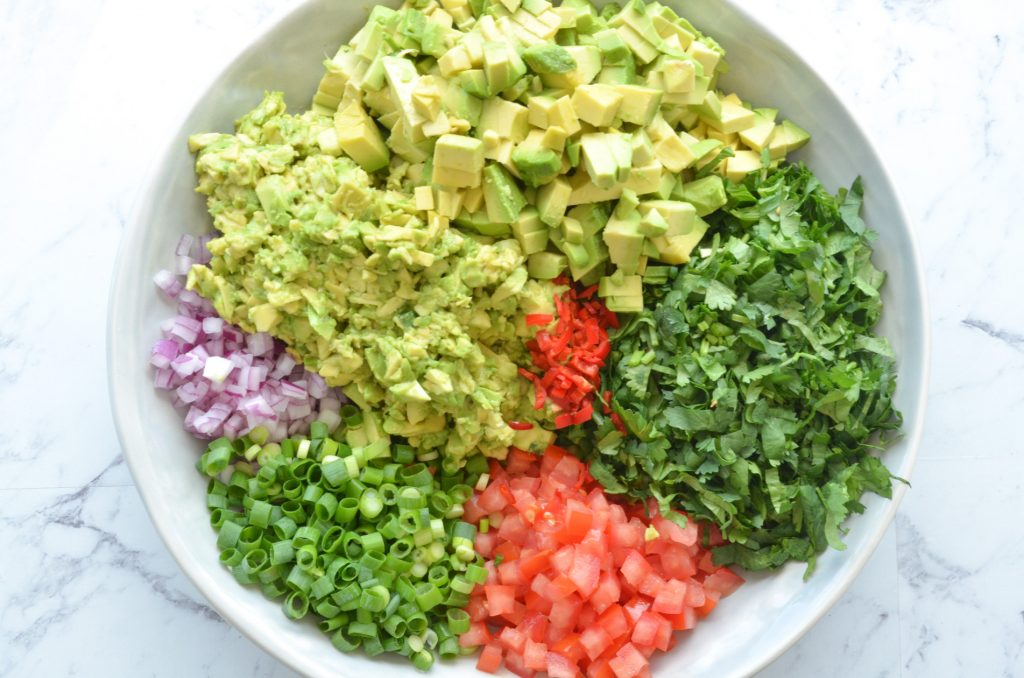 avocado dip ingredients chopped in a bowl ready to get mixed
