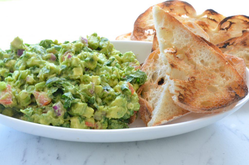 avocado dip served in a plate with bread