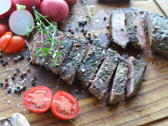 barbecued lamb backstrap served on a wooden board
