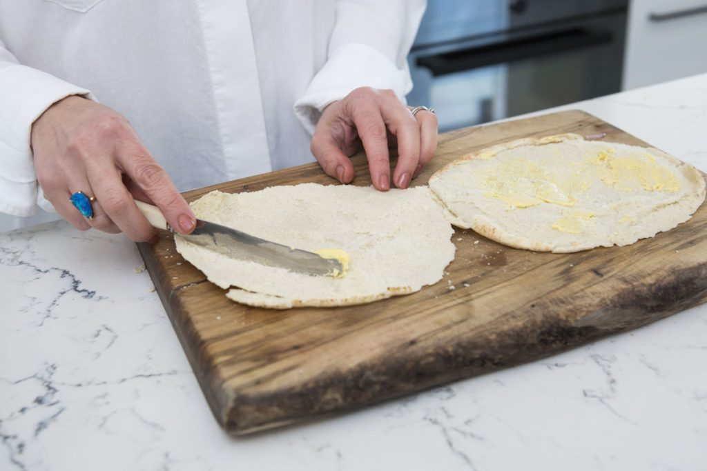 spreading butter on both sides of the pita