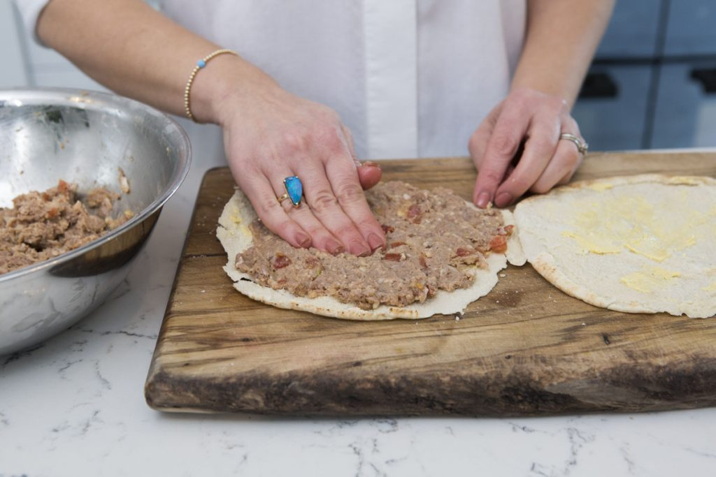 spread meat mixture on one side of the pita