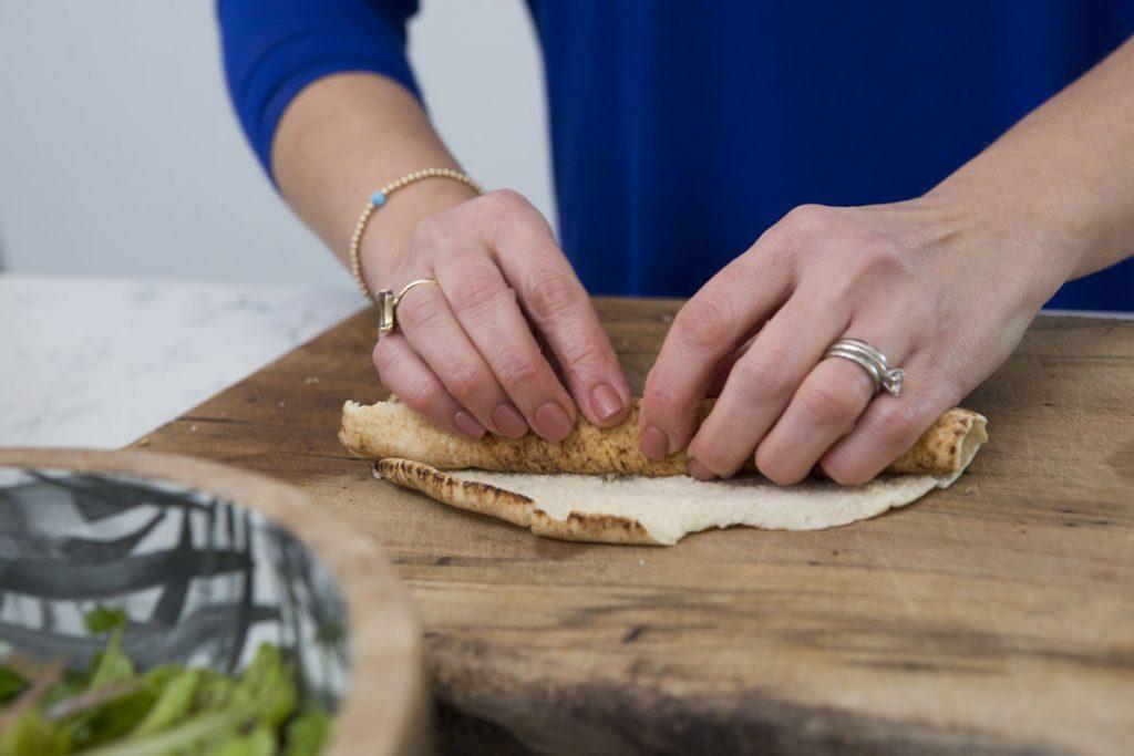 rolling arabic flat bread into a log