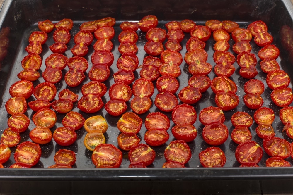 sun-dried tomato halves spread out on the baking sheet