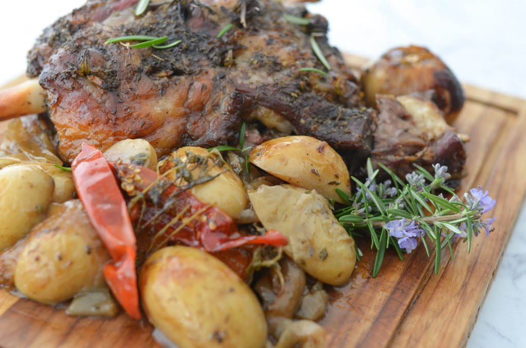 lamb roast with roast potatoes served on a wooden board