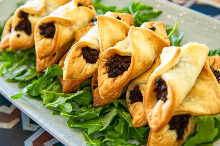 spicy lamb pastries served on a bed of rocket