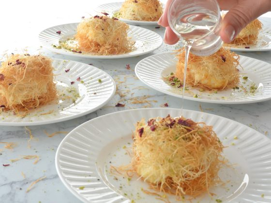 pouring sugar syrup over shredded pastry with orange blossom cream filling