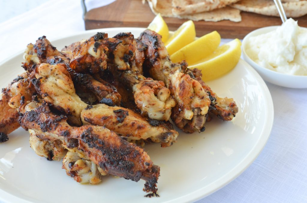 barbecued chicken wings served with lemon wedges and garlic dip
