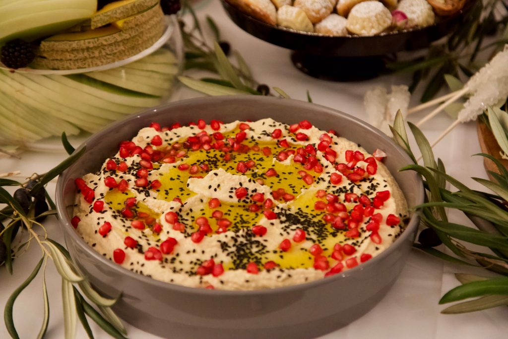 hummus garnished with black sesame and pomegranate