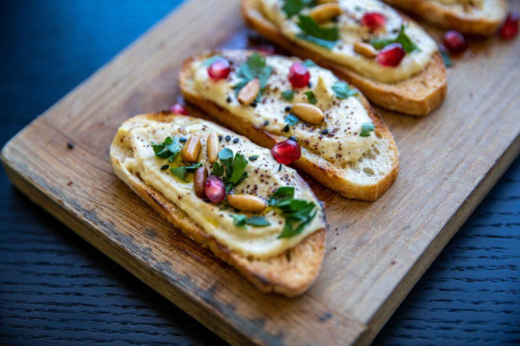 hummus bruschetta served on a wooden board