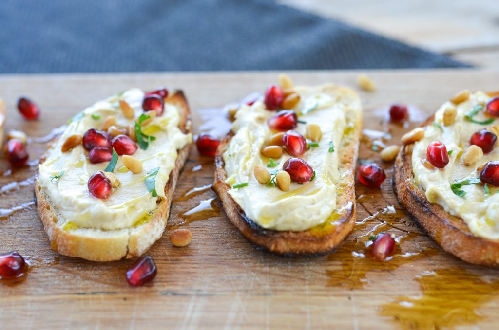 hummus bruschetta garnished with pomegranate and pine nuts