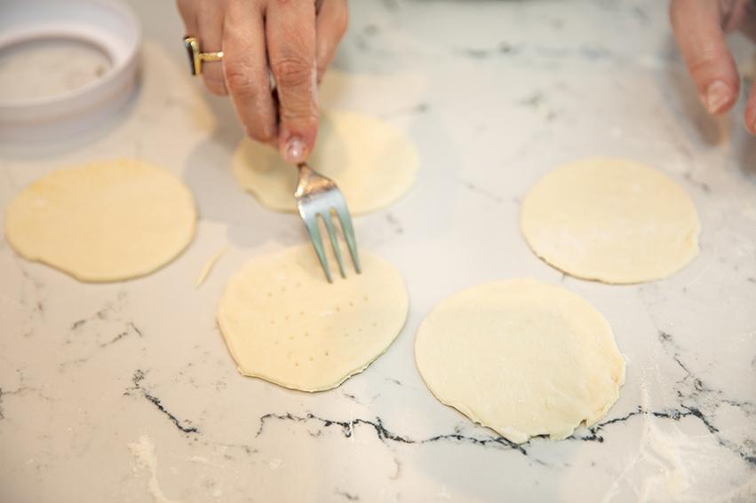 mini za'atar manoushi prick dough with a fork