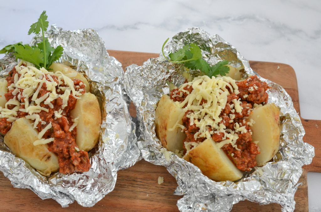 cooked baked potatoes with bolognaise sauce