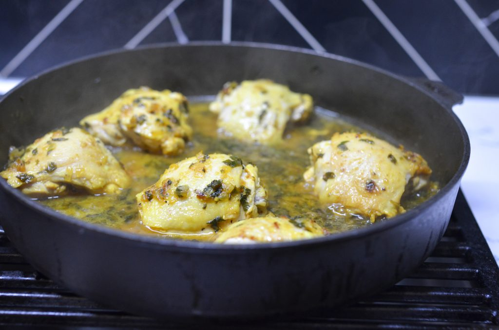 green olives and saffron chicken tagine simmering on the stove