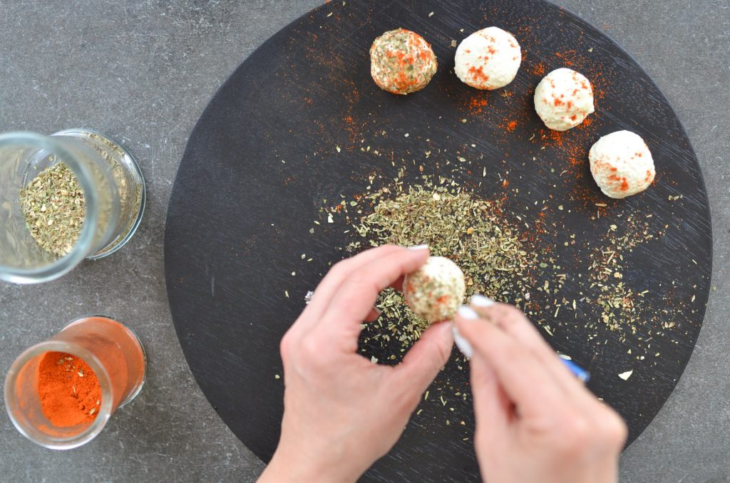 Labneh cheese bites being rolled in herbs and spices