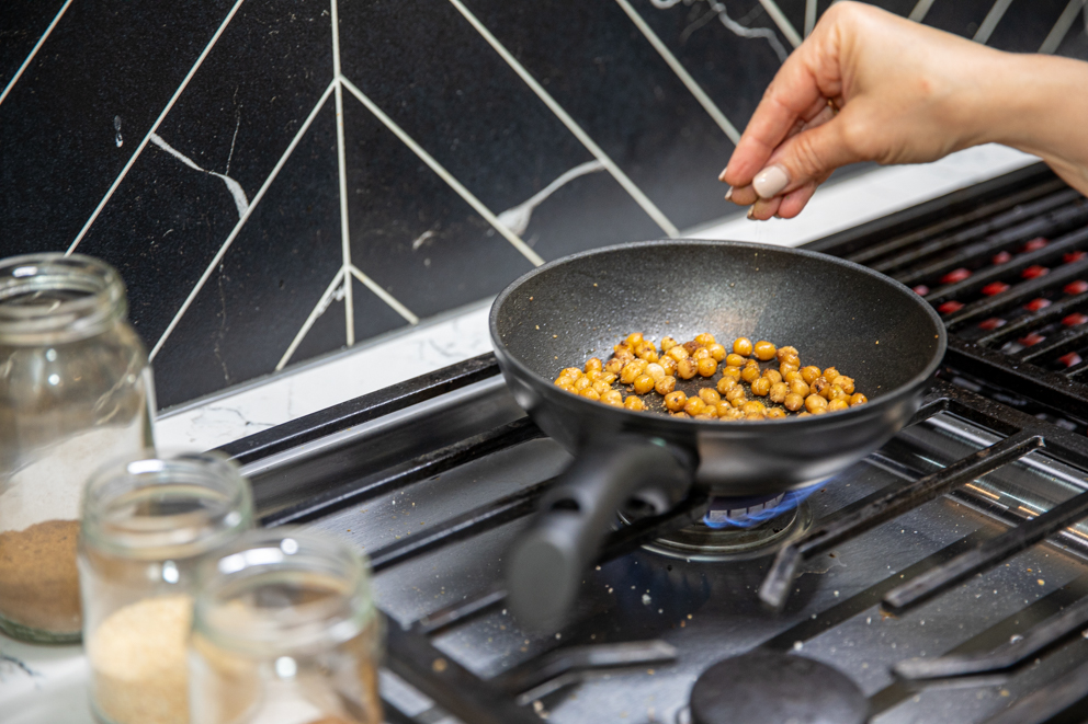 adding spices to the chickpeas - Roasted Chickpea and Hummus salad