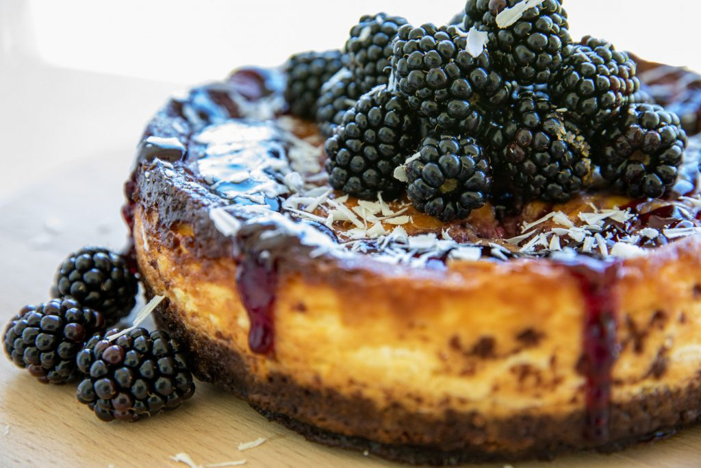 blackberry and white choc cheesecake served on a round board