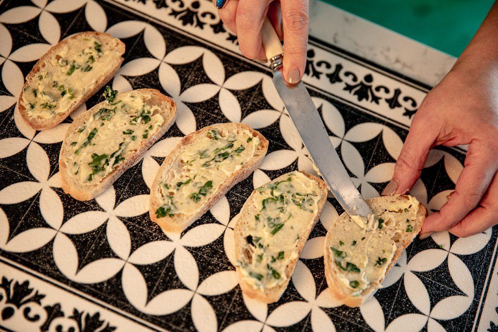 spreading garlic butter on bread