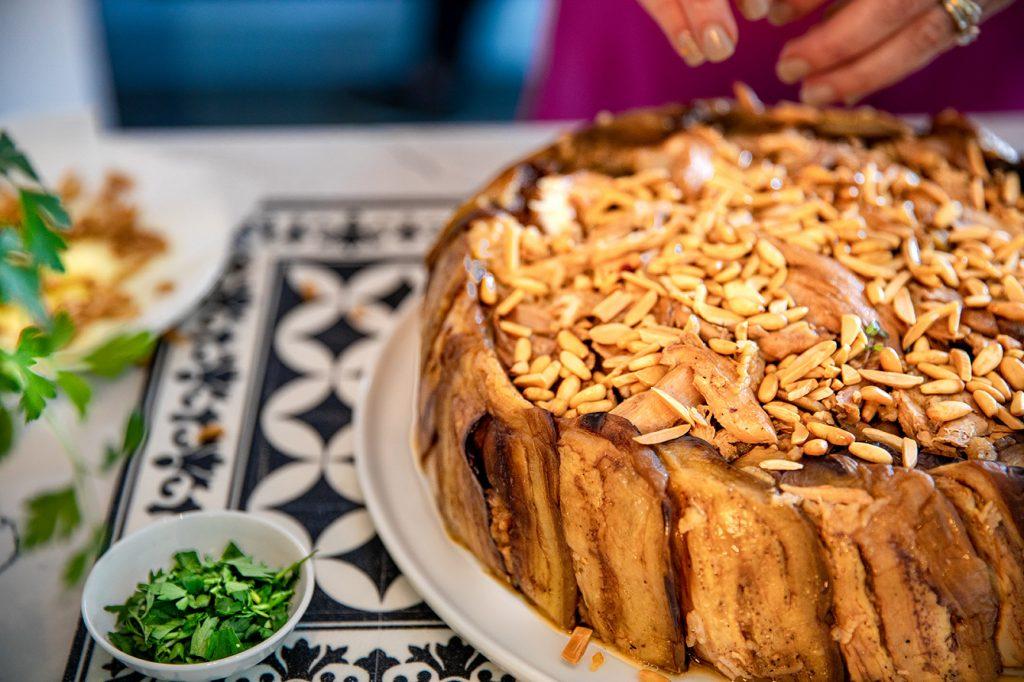 garnishing maqloubi with nuts