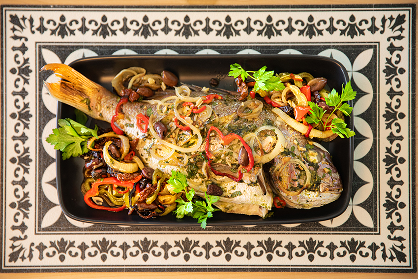 whole fish with vegetables served on black tray