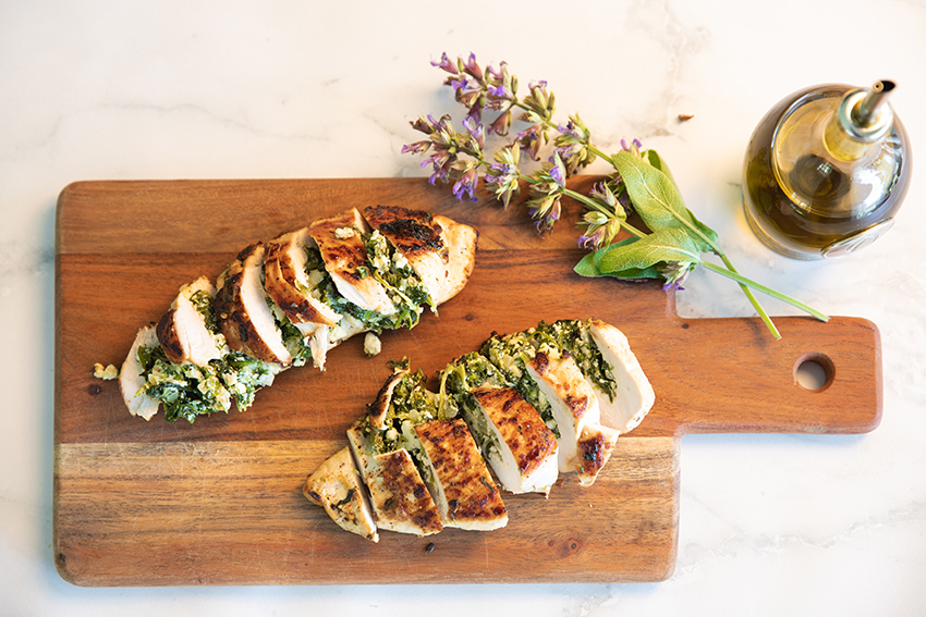 Spinach and ricotta Stuffed Chicken breast fillets served on a board with sage flowers