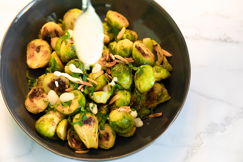 drizzling creamy tahini on brussel sprouts
