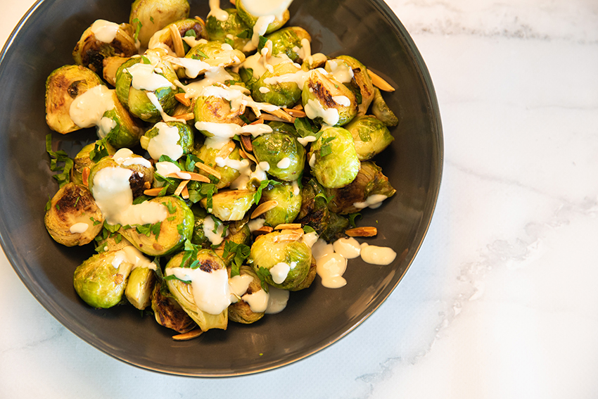 brussel sprouts drizzled with tahini sauce in a bowl