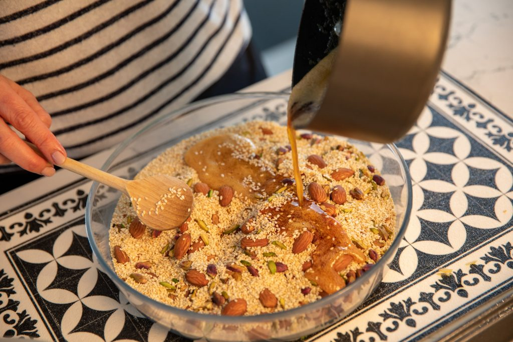 pouring honey mixture over toasted sesame and nut mixture
