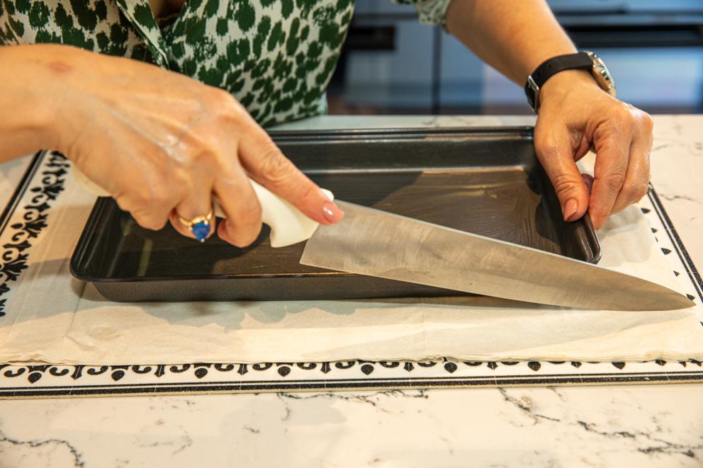 cutting the filo to the size of the tray
